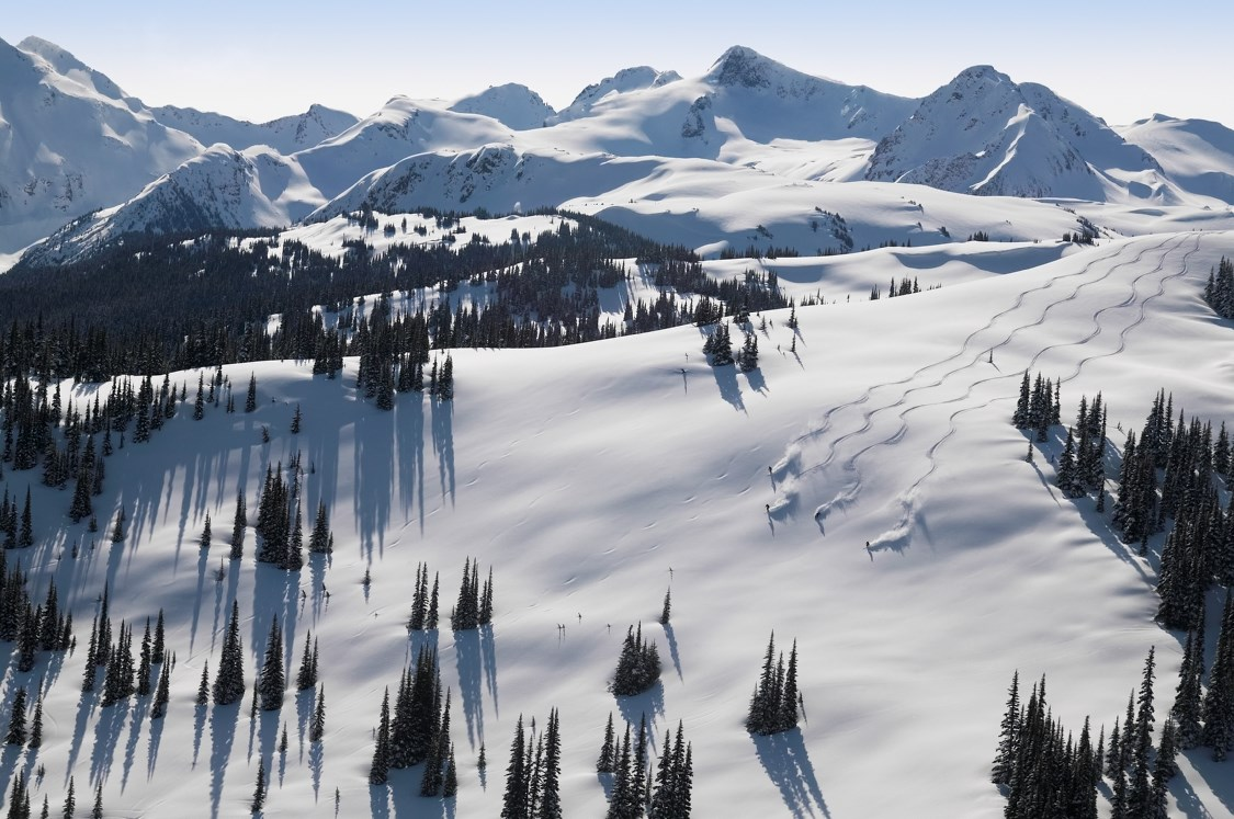 Four skiers and riders leaving fresh powder tracks at Whistler