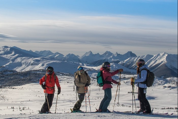 Group of skier girls with backpacks and gear on a ski trip at Lake Louise